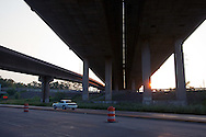 As the sun sets on a warm day in Northwest Indiana, a single car slips by on Riley Road underneath the huge concrete structure for Cline Avenue, which is now closed to traffic due to structural issues.