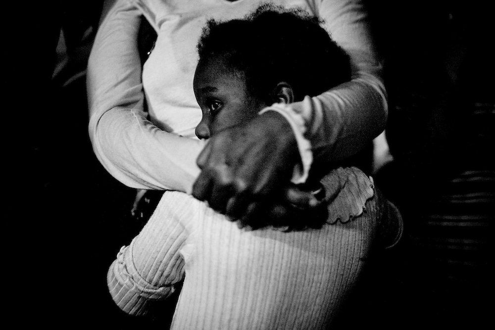 A girl hugs her mother during an outdoor evening church service to at a camp for those displaced by the recent earthquake in Petionville, outside Port-au-Prince, Haiti.