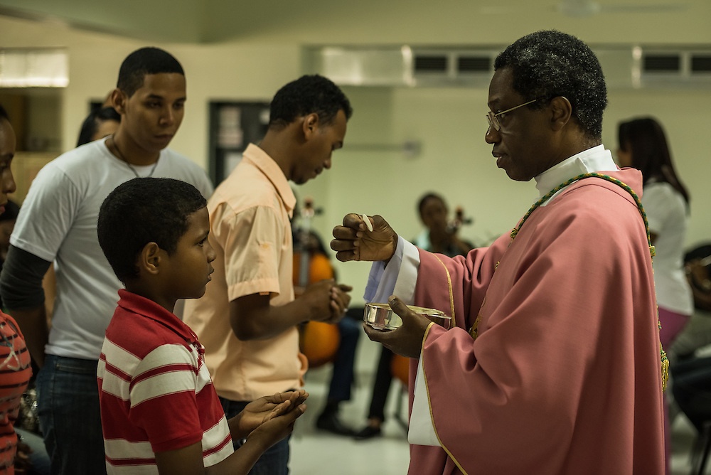 """SANTO DOMINGO, DOMINICAN REPUBLIC - MARCH 30, 2014:  Vatican nuncio to the Dominican Republic, Archbishop Jude Thaddeus Okolo gives communion to a young boy during mass for teenagers who represent the Dominican Republic during the Vatican's """"World Youth Day"""".   Okolo recently arrived in Santo Domingo to replace the previous Vatican nuncio, Josef Wesolowski, who has been accused by local officials of molesting young boys that work along the malecon here, shining shoes. Several teenagers attending the event told visitors that they had interacted with Wesolowski during local church events, and were suprised by the accusations. CREDIT: Meridith Kohut for The New York Times"""