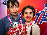 "14 FEBRUARY 2017 - BANGKOK, THAILAND: A couple waits to have their picture taken during mass weddings in the Bang Rak district in Bangkok. Bang Rak is a popular neighborhood for weddings in Bangkok because it translates as ""Village of Love."" (Bang translates as village, Rak translates as love.) Hundreds of couples get married in the district on Valentine's Day, which, despite its Catholic origins, is widely celebrated in Thailand.      PHOTO BY JACK KURTZ"