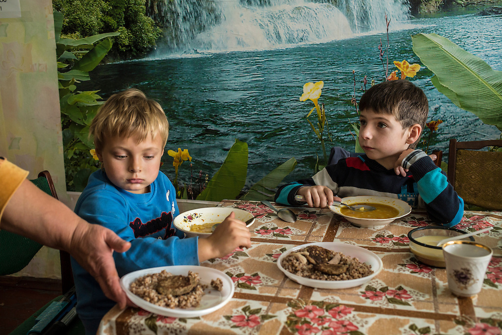 DNIPROPETROVSK, UKRAINE - OCTOBER 10: Vladik (L) and Maksim are served lunch at The Aid of Dnipro, a charity organization providing assistance to displaced people from Eastern Ukraine, on October 10, 2014 in Dnipropetrovsk, Ukraine. While the charity has received many donations of clothes and toys, they are having a difficult time providing enough food to those in need. The United Nations has registered more than 360,000 people who have been forced to leave their homes due to fighting in the East, though the true number is believed to be much higher.(Photo by Brendan Hoffman/Getty Images) *** Local Caption ***