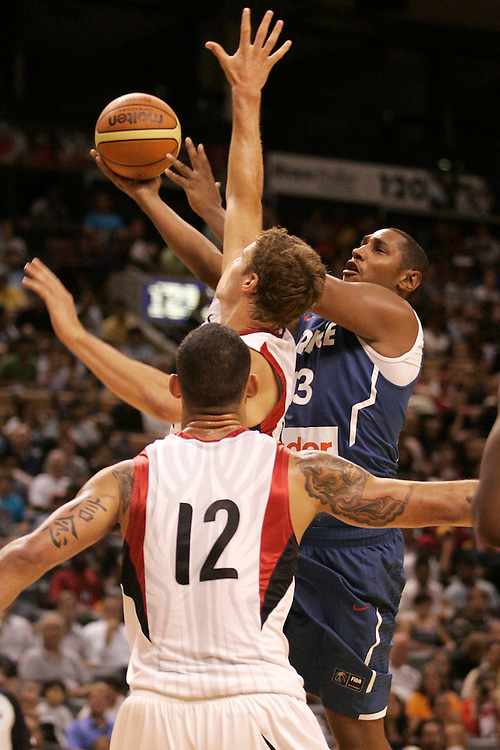 GJR505.jpg -20100812- Toronto, Ontario,Canada<br /> France's Boris Diaw, right, tries a layup past Canada's Aaron Doornekamp, top, and Robert Sacre (12) during their first matchup in the 2010 Jack Donohue International Classic tournament in Toronto, Canada August 12, 2010. Canada defeated France 69-58.<br /> AFP PHOTO/Geoff Robins