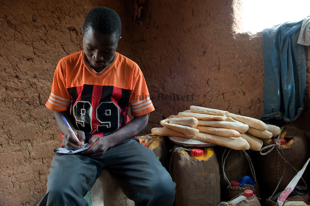 a young african migrant in a ghetto. He is preparing his traval to Libya : bread, water.