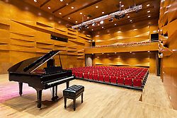 Concert hall auditorium with grand piano, rows of seats. Heino Eller's Tartu Music School in Estonia.