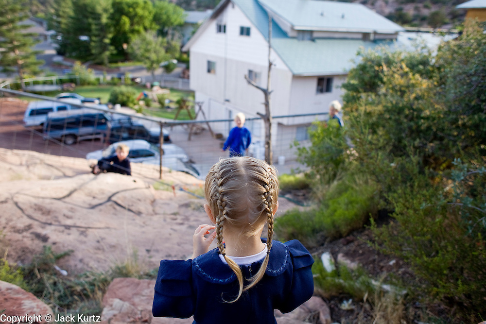 """Aug 9, 2008 -- COLORADO CITY, AZ: Jessop children play in the backyard of their home in Colorado City, AZ. Colorado City and neighboring town of Hildale, UT, are home to the Fundamentalist Church of Jesus Christ of Latter Day Saints (FLDS) which split from the mainstream Church of Jesus Christ of Latter Day Saints (Mormons) after the Mormons banned plural marriage (polygamy) in 1890 so that Utah could gain statehood into the United States. The FLDS Prophet (leader), Warren Jeffs, has been convicted in Utah of """"rape as an accomplice"""" for arranging the marriage of teenage girl to her cousin and is currently on trial for similar, those less serious, charges in Arizona. After Texas child protection authorities raided the Yearning for Zion Ranch, (the FLDS compound in Eldorado, TX) many members of the FLDS community in Colorado City/Hildale fear either Arizona or Utah authorities could raid their homes in the same way. Older members of the community still remember the Short Creek Raid of 1953 when Arizona authorities using National Guard troops, raided the community, arresting the men and placing women and children in """"protective"""" custody. After two years in foster care, the women and children returned to their homes. After the raid, the FLDS Church eliminated any connection to the """"Short Creek raid"""" by renaming their town Colorado City in Arizona and Hildale in Utah. A member of the Jessop family weeds the community corn plot in Colorado City, AZ. The Jessops are a polygamous family and members of the FLDS. Photo by Jack Kurtz / ZUMA Press"""