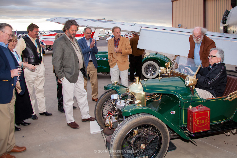 Attendees 'try on' a car, and the owner hand cranks it over, during Planes and Cars at the Santa Fe Airport, 2013 Santa Fe Concorso.