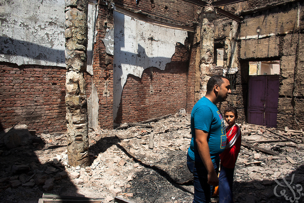 Deacon Ebraam (l), surveys damage inside the ruins of the (old) Virgin Mary Church August 20, 2013 a week after an attack by Muslims in the village of Nazla, located near el Fayoum around a 100 kilometers South of Cairo, Egypt.  Christian villagers report 2 churches and a monastery in the area came under attack by their Muslim neighbors on the same day as Egyptian security forces were moving to forcibly disperse the sit-in camp of the supporters of deposed president Mohamed Morsi.