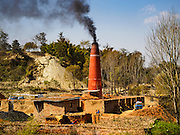 03 MARCH 2017 - BAGMATI, NEPAL: A brick factory in Bhaktapur spews smoke from coal fires that bake bricks in the kiln. There are almost 50 brick factories in the valley near Bagmati. The brick makers are very busy making bricks for the reconstruction of Kathmandu, Bhaktapur and other cities in the Kathmandu valley that were badly damaged by the 2015 Nepal Earthquake. The brick factories have been in the Bagmati area for centuries because the local clay is a popular raw material for the bricks. Most of the workers in the brick factories are migrant workers from southern Nepal.       PHOTO BY JACK KURTZ