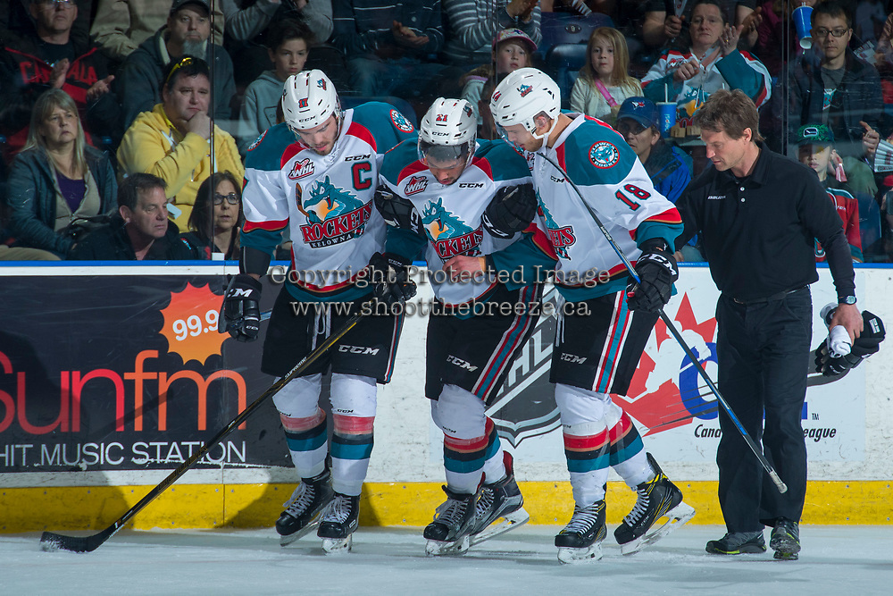 KELOWNA, CANADA - APRIL 30: Rodney Southam #17 and Carsen Twarynski #18 escort Devante Stephens #21 of the Kelowna Rockets off the ice with athletic therapist Scott Hoyer after a hit from behind against the Seattle Thunderbirds on April 30, 2017 at Prospera Place in Kelowna, British Columbia, Canada.  (Photo by Marissa Baecker/Shoot the Breeze)  *** Local Caption ***