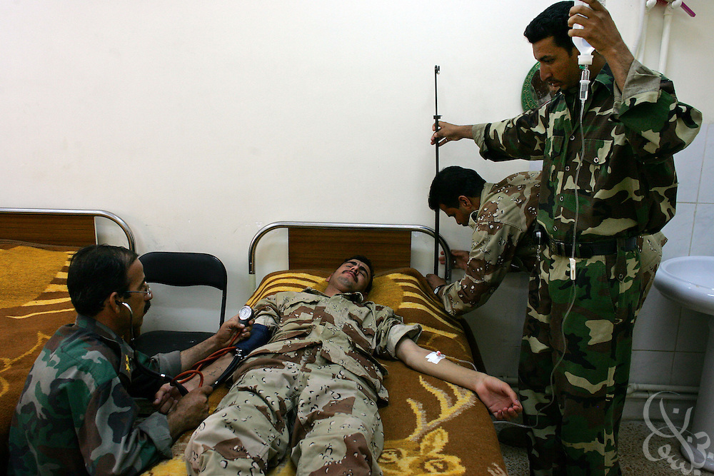 A 10th Division, 4th Brigade Iraqi army soldier is treated by his colleagues for dehydration during training  at the Sparrow Hawk base outside al-Amarah, Iraq May 27, 2006.