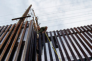 A migrant climbs a border fence into the United States from Mexicali, Mexico on Thursday, April 13, 2006.<br />