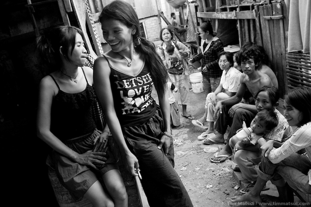 """Prostitutes Srey Dah, left, and Srey Bee, right,  relaxing before a night of work while at home in the slum where the non governmental organization """"Acting for Women in Distressing Situations"""" (AFESIP), conducts outreach and provides services in Phnom Penh, Cambodia. The permanent structure, a decaying four story building known simply as 'The Building', was built in the 1960's as transitional housing and now hosts a shantytown where many of the city's poor live, including many prostitutes, and is believed to have the highest rate of HIV infection in the city. AFESIP hands out free condoms, instructs prostitutes on HIV prevention, and conducts outreach in case the prostitutes need medical services, choose to leave their profession, or can report on cases of sex trafficking. AFESIP offers housing, education, training, and counseling for women who are victims of sex trafficking, worked as prostitutes, or are escaping domestic violence. Founded by Somaly Mam, who herself was once a prostitute and victim of trafficking and domestic abuse, AFESIP has three facilities in Cambodia and works with other NGO's to provide long term care for the women."""
