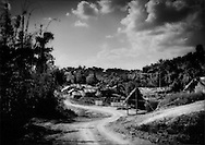 Barren Batek Negrito settlement set up by the government outside the entrance to Taman Negara National Park, sandwiched between the great protected forest and vast oil palm plantations to the north that now occupy land the Batek would live in and wander through when it was clothed in old growth rainforest not so long ago, Kuala Koh, Kelantan, Malaysia.   The settlement lacks any shade and residents often retreat from the infernal midday sun into a forest settlement where the other families from the same clan have chosen to remain and live.  Public showers can be seen in the middle of the image.