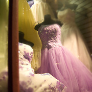 Several party dresses in thrift shop window shot at nighttime. Downtown San Diego.
