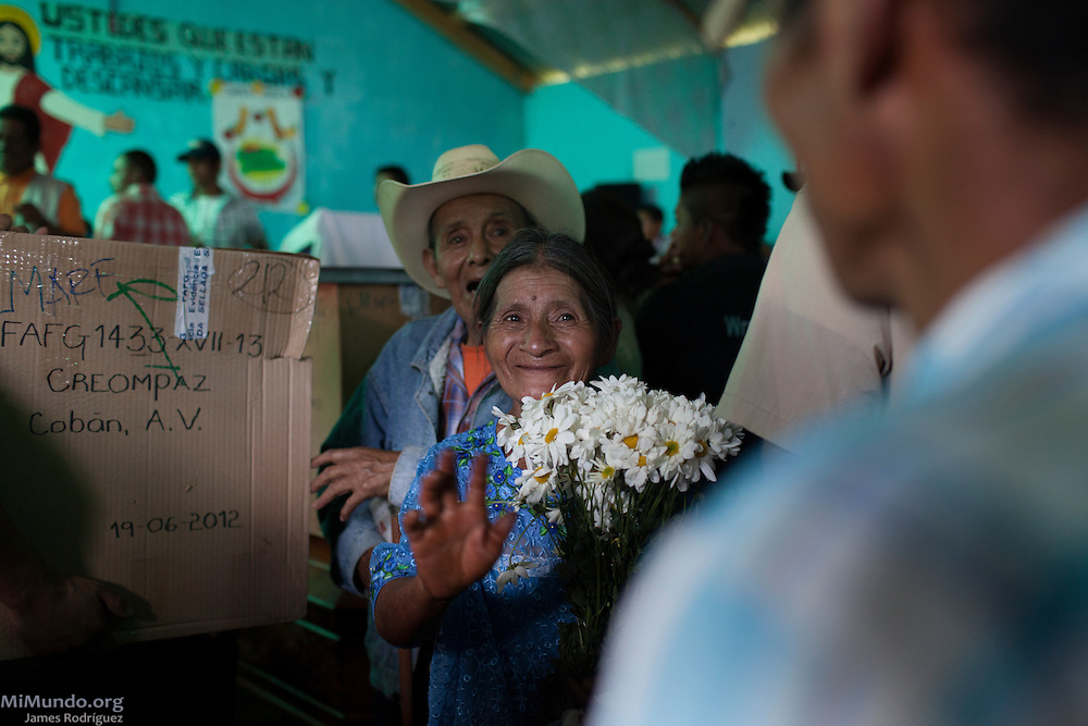 Isabela Ja (forefront) and her husband Celso Chiquin, smile after receiving the skeletal remains of their son Baldomero Chiquin Ja. The positively identified male remains of six wartime victims, including Baldomero's, are returned to their appropriate families by members of the Guatemalan Forensic Anthropology Foundation (FAFG) in the Poqomchi' Mayan hamlet of Pambach, 38 kilometers from Cobán. The remains, matched through DNA samples, were exhumed from grave 17 of the Regional Command of Training and Peacekeeping Operations (CREOMPAZ), formerly known as Military Zone 21 in Cobán. All six men were taken by the army during an incursion to the village on June 2, 1982, during the de facto government of Efraín Ríos Montt, and were never seen again. A total of 64 skeletal remains were recovered from grave 17, the majority of which bore evidence of violence such as blindfolds and bound hands and feet. Pambach, San Cristobal Verapaz, Alta Verapaz, Guatemala. November 22, 2013.