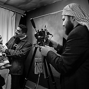 Baby Ali had to be coaxed by a photo assistant to stay awake as his passport photo was being taken in Amman, Jordan before Hadia and the children could get their visas to enter the United States.