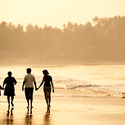 A family walking at sunset along the Goan Beach, Goa, India
