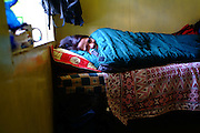 Filipino trekker Heia Natalia comfortably ensconed in a thick down-filled sleeping bag, Lobuche lodge, on the trail to the Everest Base Camp, Nepal 2007. Nepal 2007. Everest Base Camp