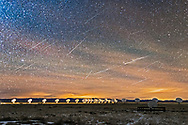The Geminid meteor shower over the Very Large Array radio telescope near Magdalena, New Mexico, on the evening of Sunday, December 13, 2015. The VLA was in its most compact &ldquo;D&rdquo; formation with the 27 dishes clustered most closely together. Lights from the control building illuminate the dishes to the left. Glows from Santa Fe and Albuquerque illuminate the horizon. This was a dark moonless night. One bright meteor left a long-lasting train the provided the fuzzy &ldquo;smoke&rdquo; trail at right. <br /> <br /> This is a stack of more than two dozen images, one providing the ground and sky and one bright meteor early in the shoot, and the rest providing additional meteors (22) captured over the 3-hour-long shoot from 8 pm to 11 pm. A total of 334 frames were shot, of which about 30 had meteors: not all are included here - some were very faint or at the edge of the frame, or overlapped other meteors, or were sporadics. <br /> <br /> I&rsquo;ve made mo attempt to position the meteors so they all emanate from the radiant point&rsquo;s position at the time the base sky image was taken. Over the 3 hours of the shoot the radiant in Gemini, off frame at right here, rose higher, causing the meteors to appear at a steeper angle. Thus, those meteors more parallel to the ground are from early in the shoot, while those at an angle more perpendicular to the ground are from later in the evening. <br /> <br /> One bright meteor right of centre appears on two frames (the shutter closed and re-opened while it was still going). This meteor left a long-lasting train that persisted on several frames that are layered in here to add the drifting &ldquo;smoke&rdquo; trail. It actually lasted over 30 frames. <br /> <br /> Each frame was a 32-second exposure at f/2 with the 35mm lens and with the Canon 6D at ISO 3200. The camera was not tracking the sky &ndash; the view is looking northwest toward the setting sky, a direction dictated by the viewing location to get the dishes in 