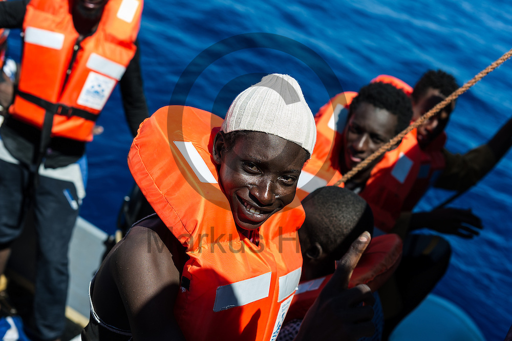 Ein Fluechtling laechelt am 22.09.2016 auf dem Fluechtlingsrettungsboot Sea-Watch 2 in internationalen Gewaessern vor der libyschen Kueste in die Kamera. Foto: Markus Heine / heineimaging<br /> <br /> ------------------------------<br /> <br /> Veroeffentlichung nur mit Fotografennennung, sowie gegen Honorar und Belegexemplar.<br /> <br /> Publication only with photographers nomination and against payment and specimen copy.<br /> <br /> Bankverbindung:<br /> IBAN: DE65660908000004437497<br /> BIC CODE: GENODE61BBB<br /> Badische Beamten Bank Karlsruhe<br /> <br /> USt-IdNr: DE291853306<br /> <br /> Please note:<br /> All rights reserved! Don't publish without copyright!<br /> <br /> Stand: 09.2016<br /> <br /> ------------------------------