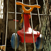 South America, Brazil. Rio de Janiero. A child's Big Wheel hangs in bars in the Favela of Vila Canoas.