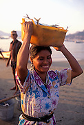 Image of a woman with freshly caught fish on the beach in Zihuatanejo, Mexico