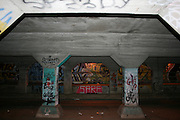 On display,in a dark underpass in Urban Atlanta, is a canvas of varied and colorful urban artwork, gang related, grafitti.