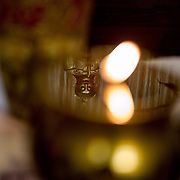 A Taoist God's reflection in an offertory candle at the Temple of the Goddess of Mercy.