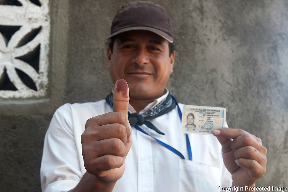 Ramon Ivon Herreda Garcia shows his cedula and thumb after placing his vote for Ortega in the 2011 elections in the town of Alta Gracias, Omptepe, Nicaragua. He says he voted for Ortega because he helps the poor, by  giving them food, and roofs on their homes.