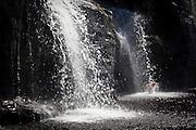 A hiker bathes under Tsusiat Falls, West Coast Trail, British Columbia, Canada.