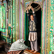 A woman lays prostrate in fron of the doorway to  Shah-i-hamadan shrine while a man looks on.