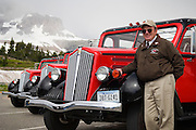 "Driver/Guide Robert Ferguson with his ""Jammer"" tour bus at Logan Pass, Glacier National Park, Montana."