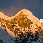 "The moon sets at sunrise over Annapurna South, seen from Annapurna South Base Camp (ABC, at 13,550 feet elevation), in the Himalaya mountain range of Nepal. Annapurna South (also known as Annapurna Dakshin, or Moditse; 23,684 feet / 7219 meters) was first climbed in 1964 by a Japanese expedition. Annapurna is Sanskrit for ""Goddess of the Harvests."" In Hinduism, Annapurna is a goddess of fertility and agriculture and an avatar of Durga."