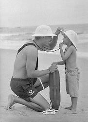 lifeguard showing a little boy how to use his whistle at the beach