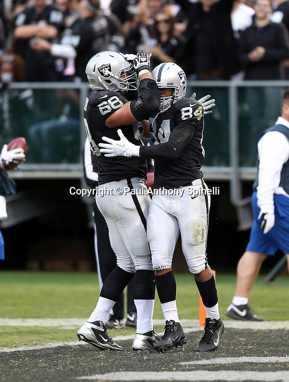 Oakland Raiders wide receiver Juron Criner (84) celebrates with Oakland Raiders tackle Jared Veldheer (68) after catching a fourth quarter touchdown pass that cuts the New Orleans Saints lead to 38-17 during the NFL week 11 football game against the New Orleans Saints on Sunday, Nov. 18, 2012 in Oakland, Calif. The Saints won the game 38-17. ©Paul Anthony Spinelli