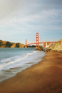 Scenic view of Golden Gate Bridge at dusk with a person and their dog on Marshall's Beach in the foreground. San Francisco, California, USA
