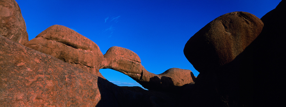 Africa, Namibia, Usakos, Setting sun lights natural granite arch overlooking Spitzkoppe rock formation in Namib Desert