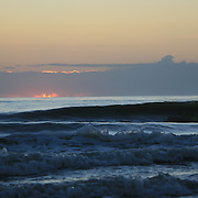 Sunrise or sunset by the sea with gentle surf crashing on the beach.