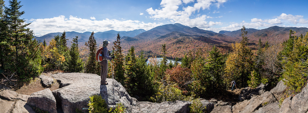 Hike Mount Jo in the Adirondack Mountains, near Lake Placid, North Elba, New York, USA. Beautiful Heart Lake and Adirondak Loj (an historic lodge) lie at the foot of Mount Jo (2876 ft or 877 m elev), which is on land owned by the Adirondack Mountain Club (AMC). With a sweeping vista of the Great Range, Mt Jo offers one of the best views for the effort in the Adirondacks: ascend 710 feet or 216 m from the Loj in 2.6 miles roundtrip. From atop Mt. Jo, see the surrounding High Peaks Wilderness Area, a state Forest Preserve protected within Adirondack Park. Adirondack Park is the largest park in the contiguous USA and is the largest National Historic Landmark. Geologic history: The Adirondacks are very new mountains from old rocks, uplifting in a circular dome (160 miles wide and 1 mile high) over just the past 5 million years. Geologically, the Adirondacks are NOT in the Appalachians: instead, they are part of the Canadian Shield (or Laurentian or Precambrian Shield which underlies half of Canada). The Adirondacks are still rising fast, up to 3 mm per year, with a central core (High Peaks region) of intrusive igneous rock, Anorthosite (not common at Earth's surface but common on the Moon's surface), surrounded by a massive dome of 1-billion-year-old metamorphic gneiss rock, in turn surrounded by some younger sedimentary rocks. In contrast, the unrelated Appalachians have mostly younger sedimentary rocks, yet are among the world's oldest mountains and are no longer uplifting.  The panorama was stitched from 9 overlapping photos.
