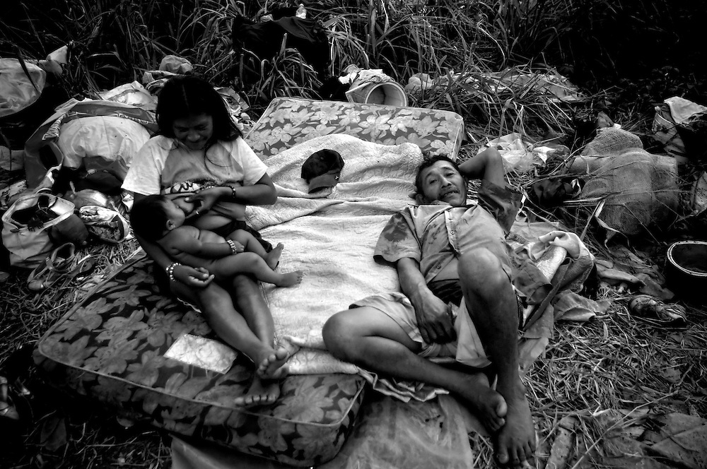 Yanira Gomez, 20, (left) feeds her four-month old baby, David, while resting with her husband, Cesario Gomez, 45, on a mattress they found in the Cambalache garbage dump in Ciudad Guayana, in northeastern Venezuela. Many Warao start salvaging recyclables, clothing and discarded food in Cambalache as early as 4am. In an effort to escape poverty, hunger and to be closer to health care facilities, approximately 300 Warao indigenous persons from the Delta Amacuro have settled in Ciudad Guayana. Although Warao community leaders say their quality of life is improved in comparison to the conditions in the Delta, the Warao are still plagued by hunger and diseases consequential of the unsanitary conditions of living and working in Cambalache.