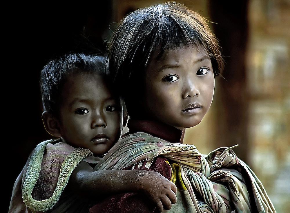 A girl cares for her brother near Luang Prabang, Laos.