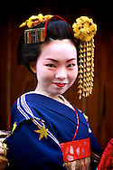 A Geisha poses for a portrait in a small Kyoto, Japan, alleyway.