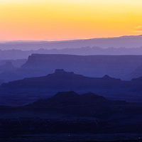 The brightening morning sky silhouettes distant ridges beyond Buck Canyon and the White Rim mesa in Canyonlands National Park, Utah.