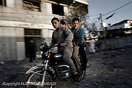 Gaza City: Young Palestinians ride a motorcycle on rubble of overnight Israeli airstrikes. November 18, 2012. ALESSIO ROMENZI