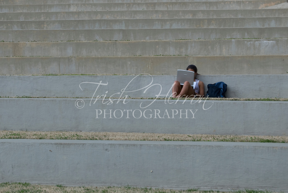 A female college student studies with her laptop in an outdoor amphitheater.