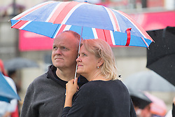 Trafalgar Square, London, June 12th 2016. Rain greets Londoners and visitors to the capital's Trafalgar Square as the Mayor hosts a Patron's Lunch in celebration of The Queen's 90th birthday. PICTURED: A couple brave the rain to watch the stage performances.