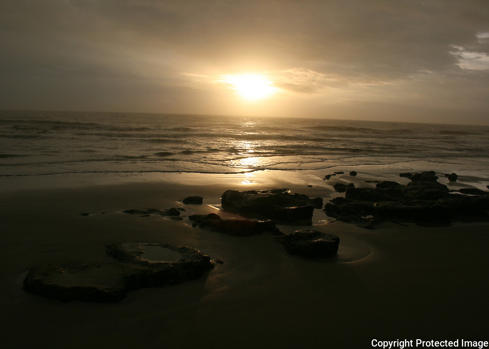 A golden sunrise, sunset, on a Jekyll Island beach with coral rock formations jutting up from the sand.