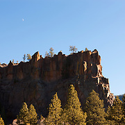 The crescent moon hovers over Battleship Rock, a 7018 foot (2139 meter) mountain in Sandoval County, New Mexico. Like other peaks in the Jemez Mountains, it was caused by a slip along a fault line.