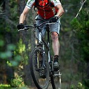 M.O. Alford, 35, of Nederland, Co. rides off a log stump laying on the ground in the West Magnolia Trail System near Nederland on Wednesday August 2, 2006. The eight to ten miles of trails in the system were ridden illegally for a number of years until the Forest Service incorporated the trails into their system about two years ago. Alford volunteers with the Boulder Mountain Bike Patrol (part of the Boulder Mountain Bike Alliance) on weekends to educate riders about access issues in the area and ensure resource conservation in the area..(MARC PISCOTTY/ © 2006)