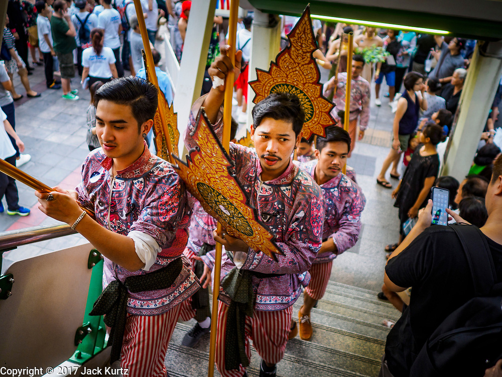 "08 APRIL 2017 - BANGKOK, THAILAND: Entertainers go up the stairs into the Phrom Phong BTS station at the ""Amazing Songkran"" festival in Benchasiri Park in Bangkok. The festival was sponsored by the Tourism Authority of Thailand to highlight the cultural aspects of Songkran. Songkran is celebrated in Thailand as the traditional New Year's Day from 13 to 16 April. Songkran is in the hottest time of the year in Thailand, at the end of the dry season and provides an excuse for people to cool off in friendly water fights that take place throughout the country. Songkran has been a national holiday since 1940, when Thailand moved the first day of the year to January 1. Songkran 2017 is expected to be more subdued than Songkran usually is because Thais are still mourning the October 2016 death of revered King Bhumibol Adulyadej.       PHOTO BY JACK KURTZ"